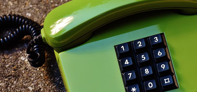Green and black corded home phone in close-up photography