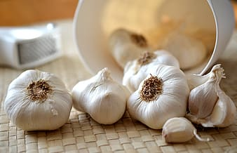 Bulbs of garlic on brown woven mat