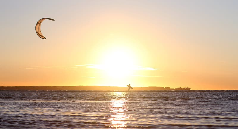 Person riding on boat on sea during sunset