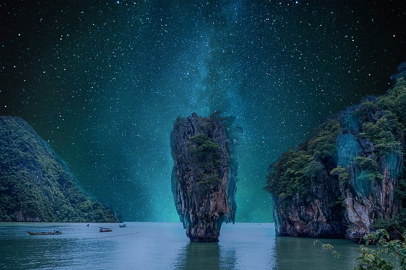 Brown rock formation on sea water during night time
