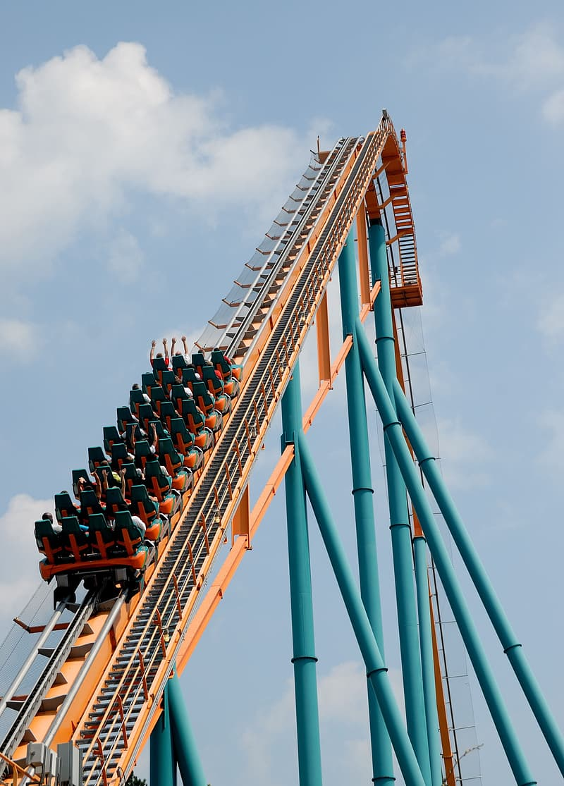 People riding roller coaster going up