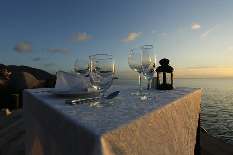 Four empty wine glasses on white tablecloth near body of water at golden hour