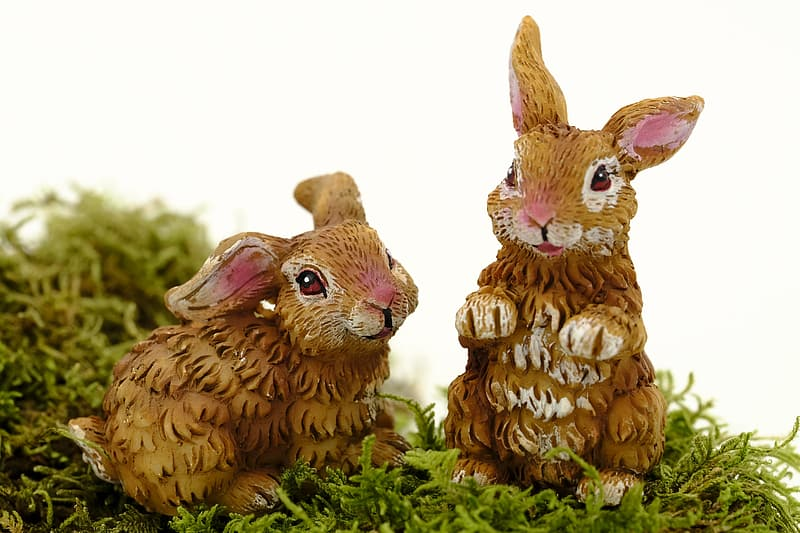 Two brown rabbit figurines on green grass