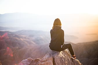 Woman in black jacket sitting on rock during daytime