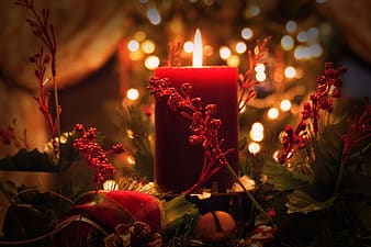 Red pillar candle surrounded by artificial plant decor