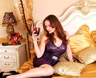 Woman holding a red wine glass in bed