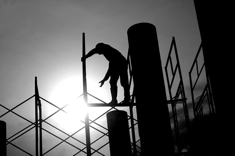 Silhouette photography of man standing on scaffold