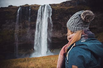 Woman in black and white polka dot shirt and black backpack standing near waterfalls during daytime