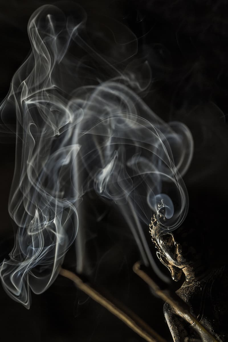 Smoke in front black buddha statue