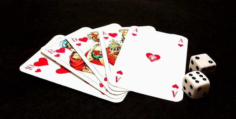 Two white die beside playing cards