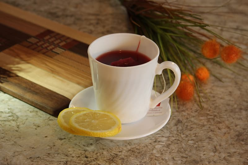White teacup and saucer with sliced lemon