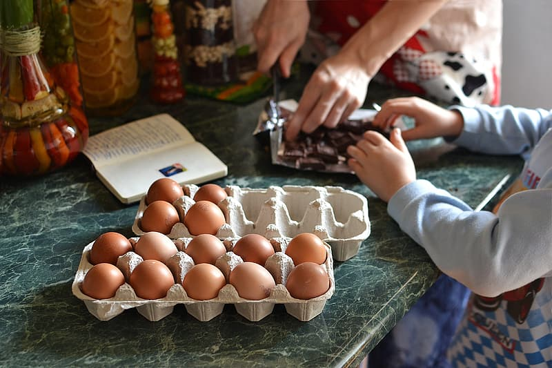 Pile of organic eggs on tray on green tile table