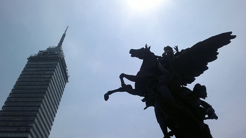 Silhouette of people riding horse statue