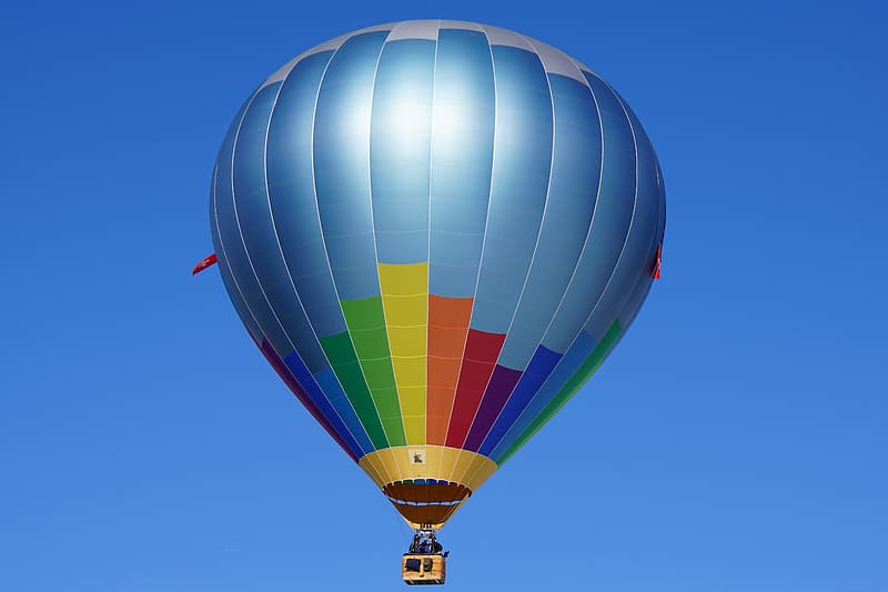 Blue, yellow, and orange hot air balloon in flight at daytime