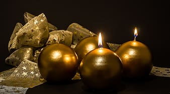 Four gold-colored candles beside brown textile