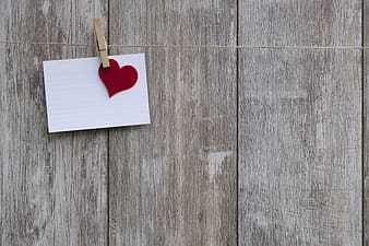White printer paper and red paper heart cutout clipped by clothes pin photograph