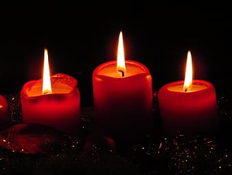 Three red lighted votive candles