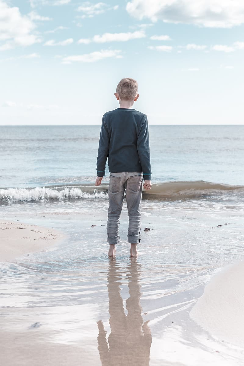 Boy on seashore during day time