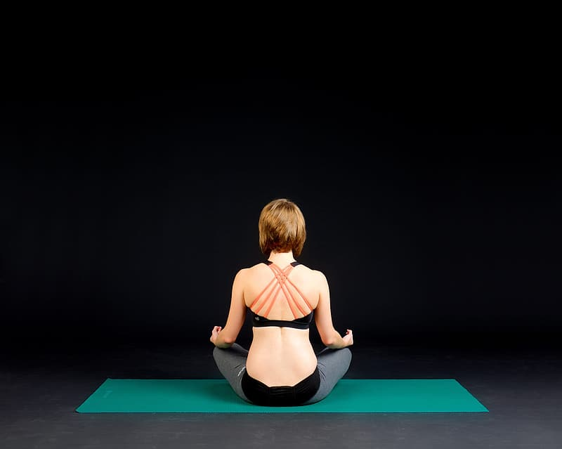 Woman in black sports bra and black panty kneeling on blue yoga mat