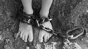 Grayscale photography of person with chain on both feet