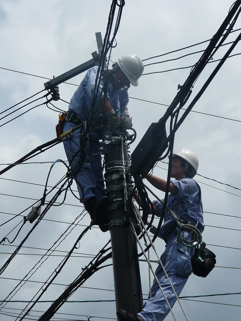 Two linemen repairing cables on utility post