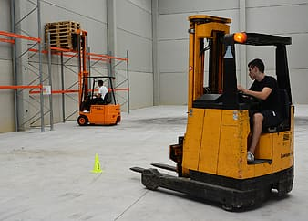 Photo of two men in forklifts