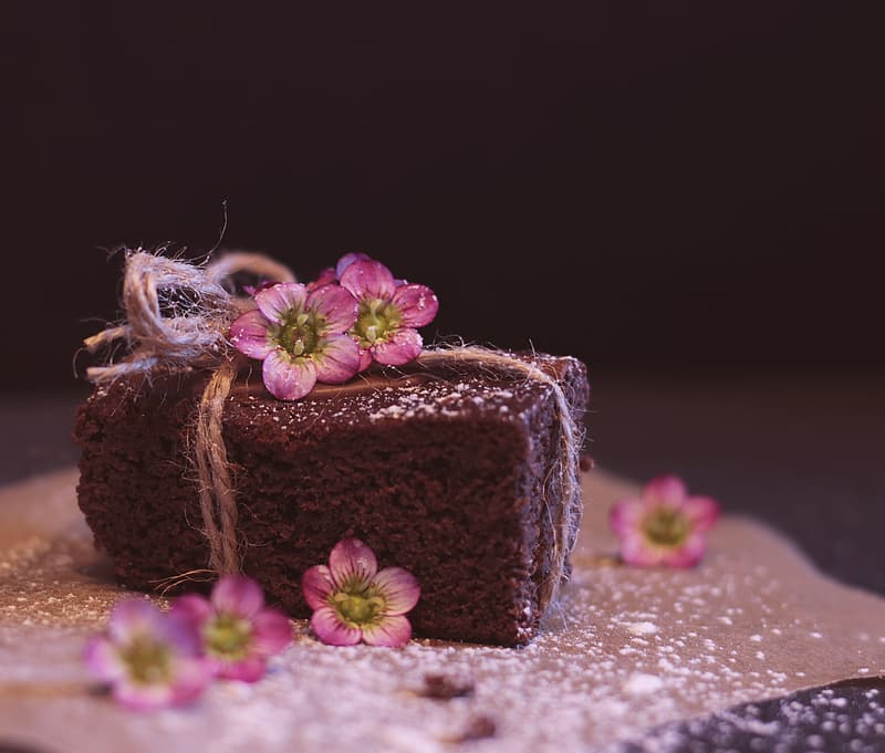 Brown cake on white and pink floral table cloth