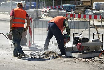 Two men fixing the road