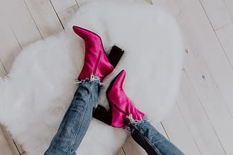 A woman in pink boots and blue jeans