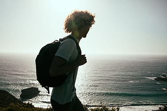 Man carrying backpack with sea below