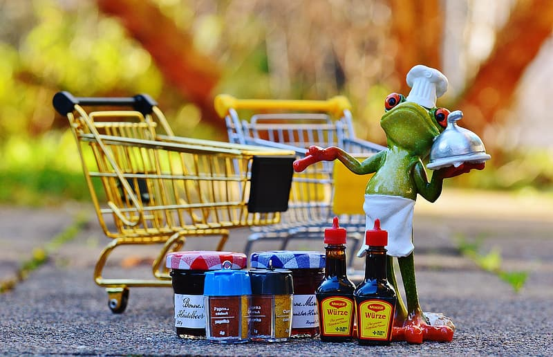 Green frog holding shopping cart figurine | Pikrepo