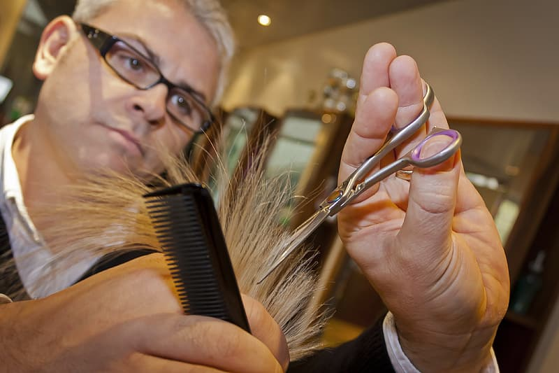 Man trimming hair using scissors and comb