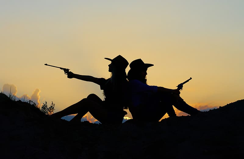 Silhouette of two cowgirl holding pistols