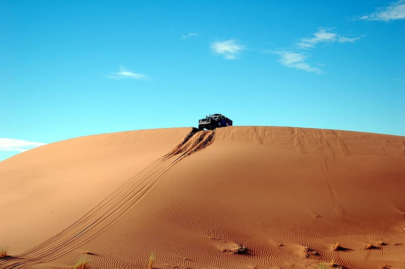 Black vehicle riding on desert
