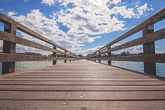Brown wooden dock under cloudy blue sky