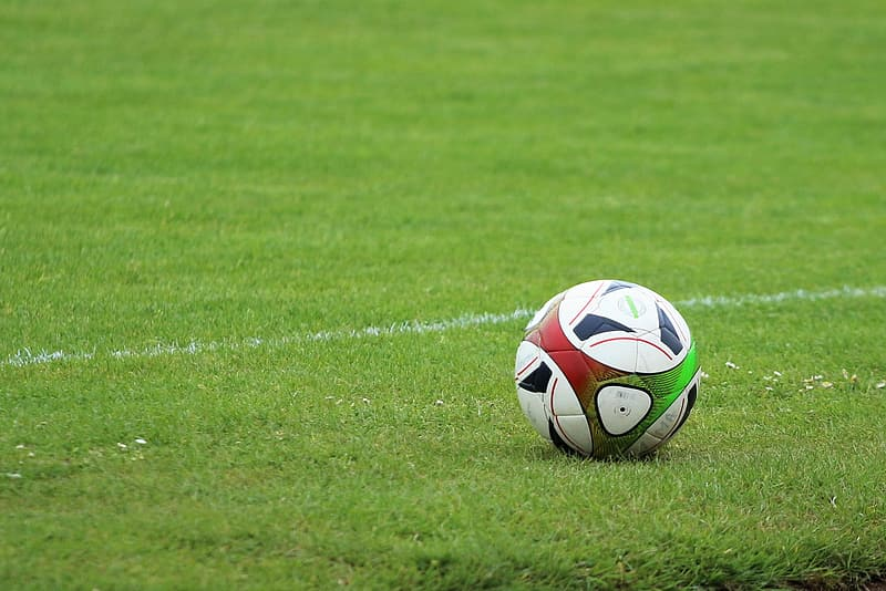 White red and blue soccer ball on green grass field during daytime