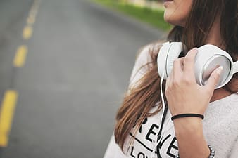 Woman in white and black shirt using white headphones