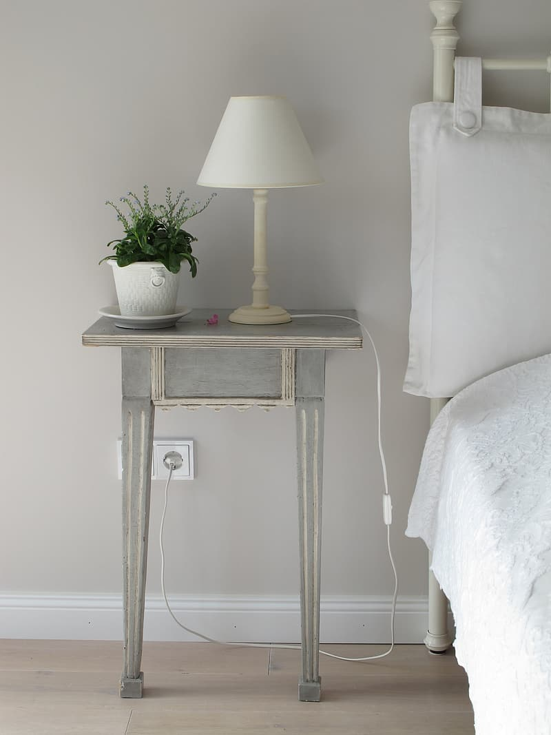 White table lamp near white pot on grey wooden end table