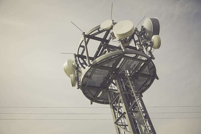Gray and white communication tower under cloudy sky