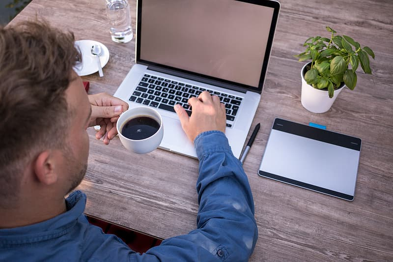 Person holding teacup in-front of laptop