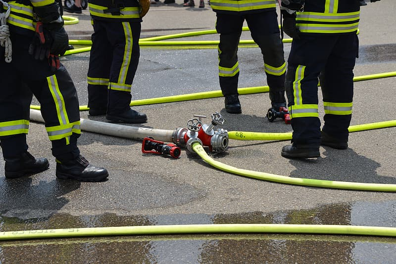 Fireman near hose on concrete pavement during daytime
