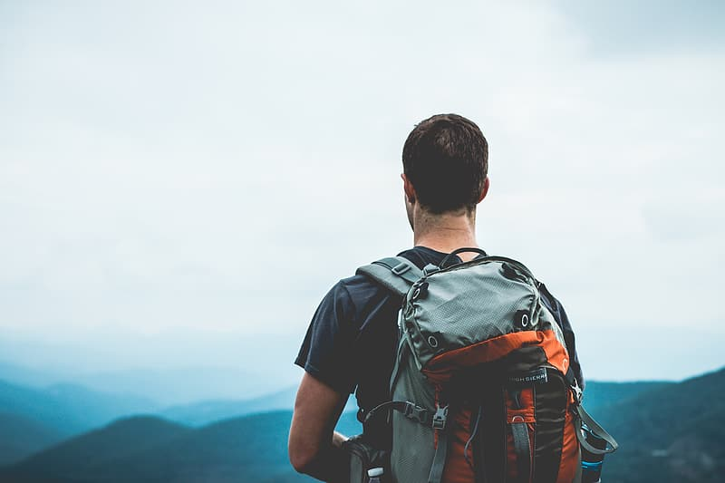 Man with backpack on top of mountain