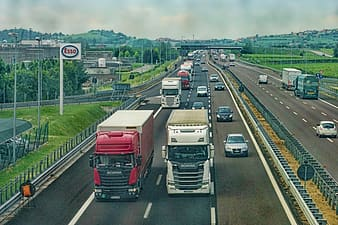 Two white and red trucks running on road