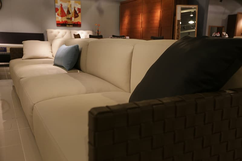 White leather 4-seat sofa with pillows in living room