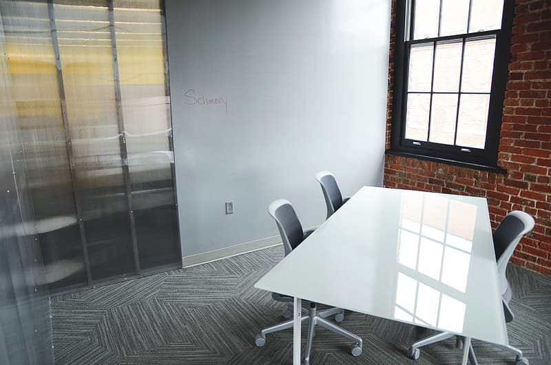 Rectangular white wooden table with three vacant rolling chairs