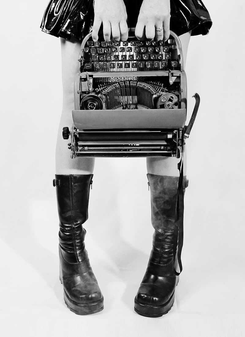 Grayscale photograph of person holding type writer machine