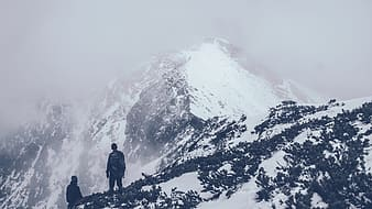 Man in black jacket standing on snow covered mountain during daytime