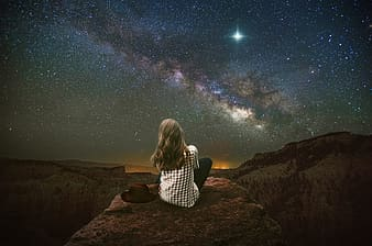 Woman in black and white checkered dress sitting on brown rock looking at stars during night