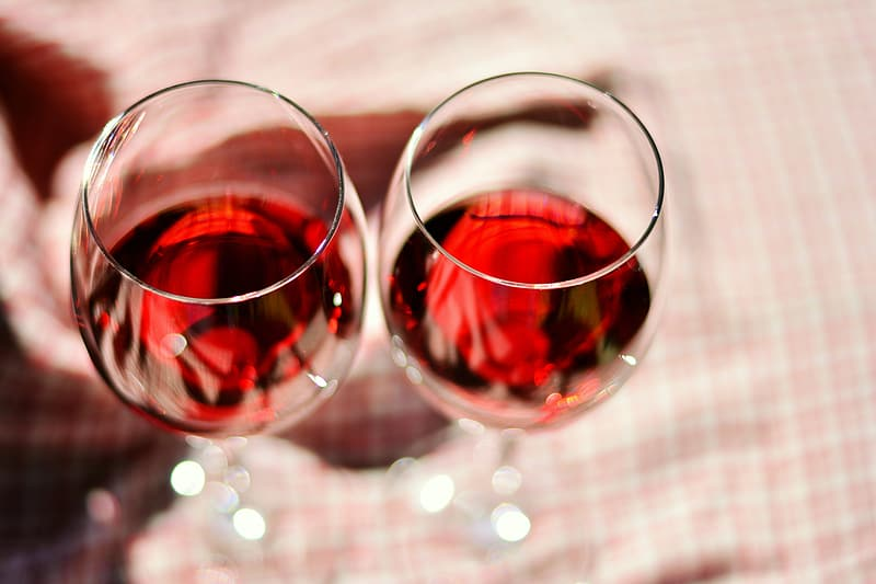 Two clear wine glasses half-filled with red wine
