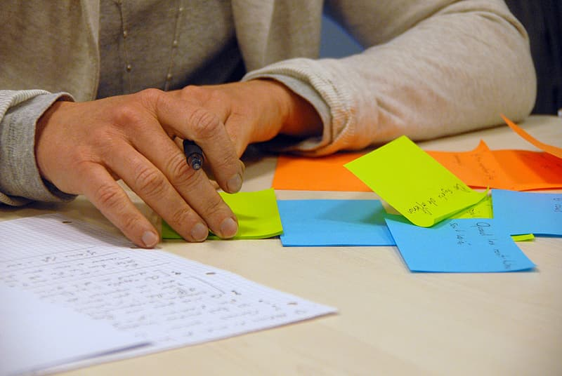 Person with assorted-color sticky notes